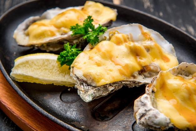 Oesters in een pan in een romige saus en kaas