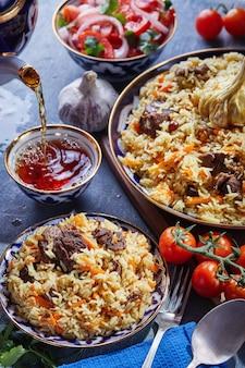 Oezbeekse pilaf in een authentieke blauwe en gouden schotel, geschoten op een blauwe achtergrond met tomaten, knoflook en thee