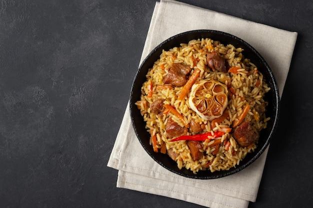Oezbeekse pilaf of plov van rijst en vlees in een gietijzeren pan. bovenaanzicht met kopieerruimte.
