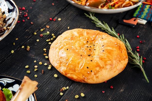 Oezbeekse platte taart lepeshka op de donkere houten tafel