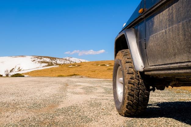 Off-road 4x4 auto in de besneeuwde bergen op een zonnige dag.
