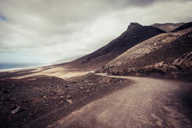 Off-road avonturenweg in de bergen met uitzicht op het strand in een wild schilderachtig landschap voor een alternatieve reisvakantie in de buitenlucht