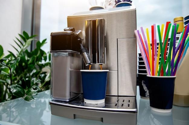 Offee machine maakt koffie. plastic blauwe beker