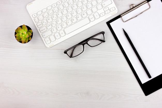 Office flatlay met wit toetsenbord, leesbril, huisdier en notebook