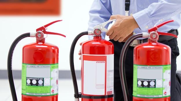 Office man het handvat van de tank van de rode brandblussers in het gebouw controleren