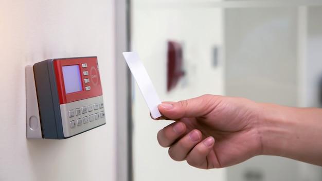 Office man met id-kaart om te scannen op toegangscontrole systeem machine
