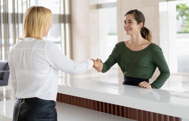Office-receptioniste groet zakelijke partner