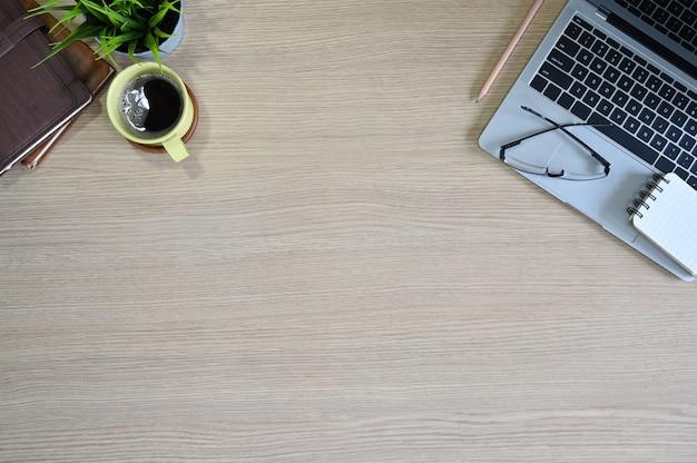 Office tafel bovenaanzicht houten tafel met laptop, glazen, koffie en kantoorbenodigdheden.