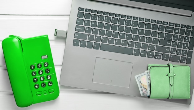 Office telefoon, laptop, flash drive, portemonnee op een witte houten tafel