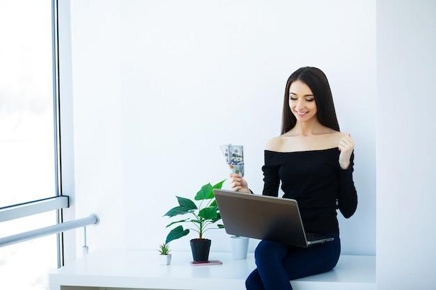 Office zakenvrouw glimlachend en zittend op de tafel.
