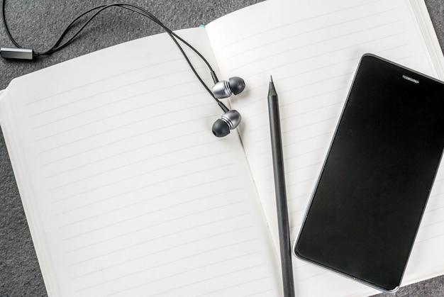 Office, zwarte desktop met apparaten. . kladblok, pennen (potloden), smartphone en koptelefoon op de tafel.