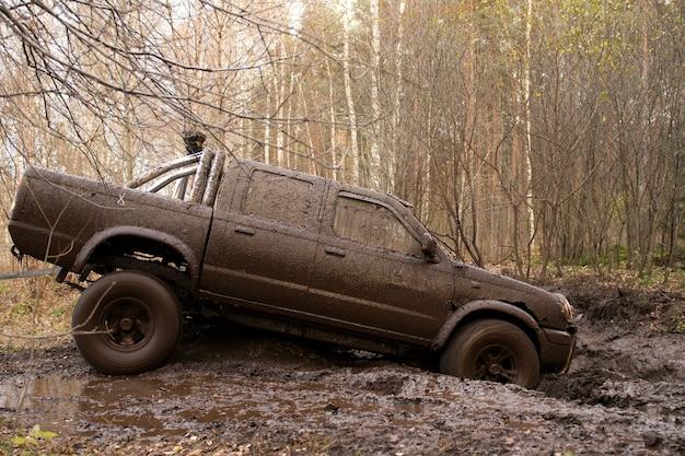 Offroad auto die door diepe moddergaten gaat detail van vuile auto met gevuld modder carwash concept
