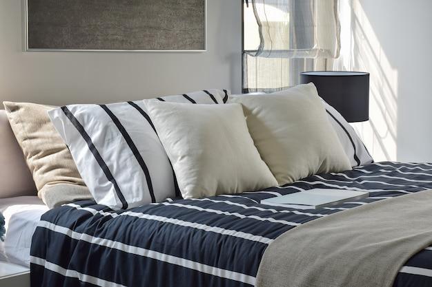 Offwhite en gestreepte hoofdkussens op bed met diep blauwe gestreepte deken in moderne stijlslaapkamer