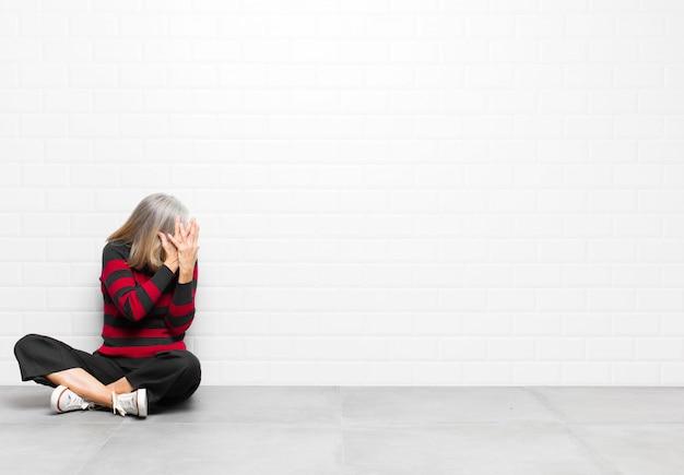 Ogen bedekken met handen met een droevige, gefrustreerde blik van wanhoop, huilen, zijaanzicht