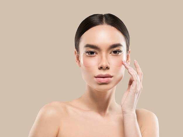 Ogen maskeren aziatische vrouw gezicht cosmetica. kleur achtergrond. bruin.