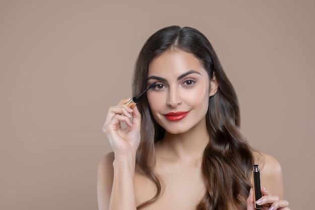 Ogen, wimpers. vrij donkerharige vrouw met blote schouders met rode lippen wimpers verven met mascara