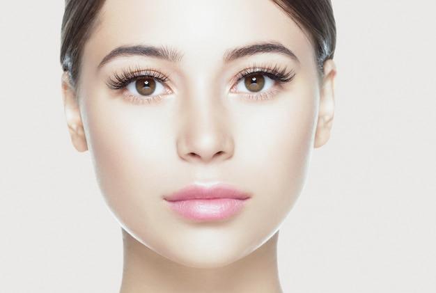 Ogen wimpers vrouw gezicht close-up natuurlijke make-up gezonde huid. studio opname. kleur achtergrond.