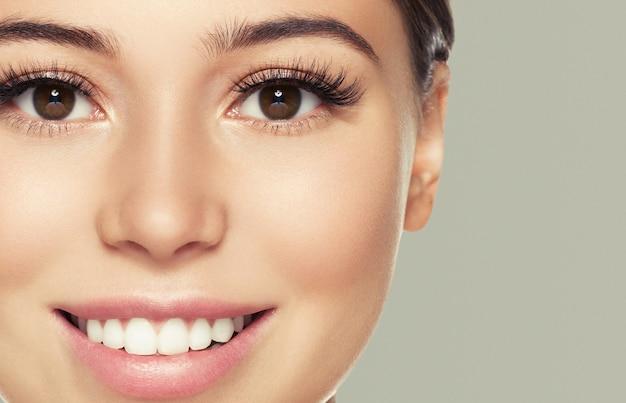Ogen wimpers vrouw gezicht close-up natuurlijke make-up gezonde huid. studio opname. kleur muur.