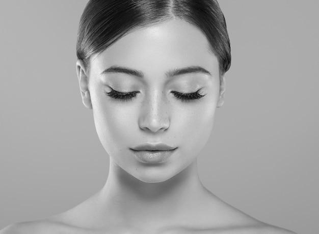 Ogen wimpers vrouw gezicht close-up natuurlijke make-up gezonde huid. studio opname. monochroom. grijs. zwart en wit.