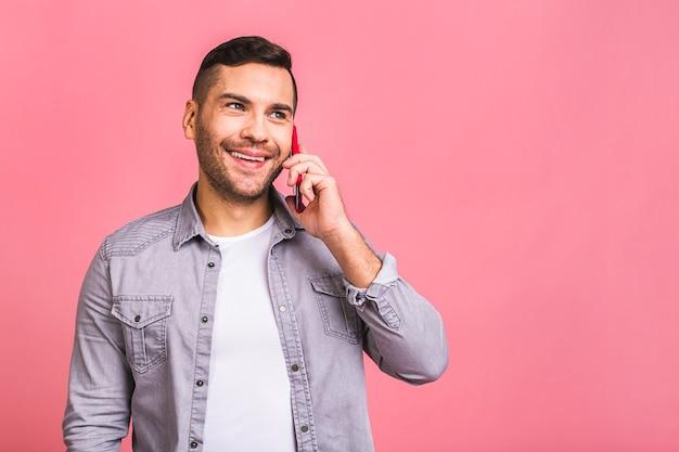 Oh, geweldig nieuws glimlachende casual jongeman praten over de mobiele telefoon. met behulp van telefoon.