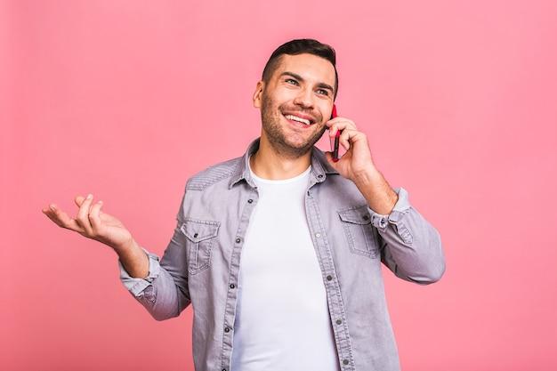 Oh, geweldig nieuws glimlachende casual jongeman praten over de mobiele telefoon