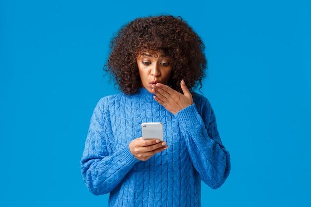 Oh god. onder de indruk en geschrokken jonge afro-amerikaanse vrouw die schokkend nieuws leest