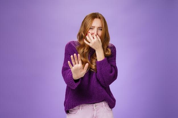 Oh god, wat stinkt weg, vies. portret van een walgelijke en ontevreden roodharige vrouw die de hand naar de camera trekt in een afwijzingsgebaar terwijl ze de neus sluit en geen vreselijke geur ruikt die loenst van afkeer.