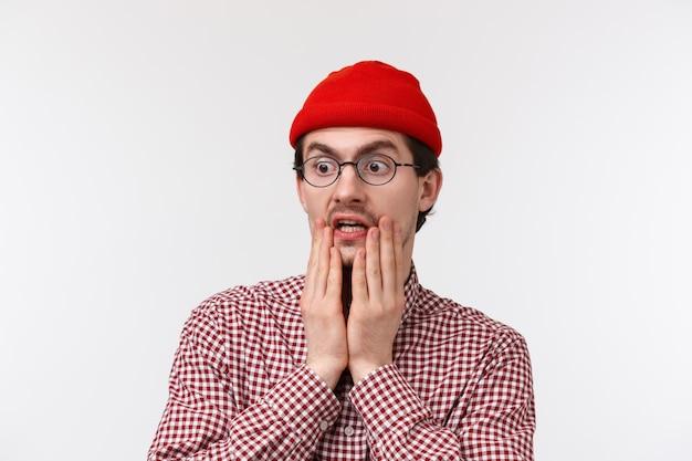 Oh goh omg verrast en sprakeloos hipster man met baard in rode muts, bril, hijgend staren naar iets schokkend grof, kijk naar links verschrikkelijk ding, staand