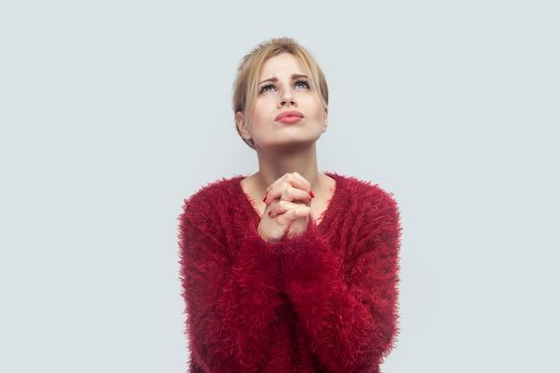 Oh mijn god, help me alsjeblieft. portret van een bezorgde, trieste, mooie jonge blonde vrouw in een rode blouse die met palmhanden staat, bidt en omhoog kijkt. indoor studio opname geïsoleerd op lichtgrijze achtergrond.
