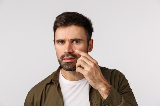 Oh mijn god is die rimpel, acne. gefrustreerde en gealarmeerde ontevreden knappe bebaarde man raakt zijn gezicht aan en onderzoekt de huid, heeft wallen onder de ogen