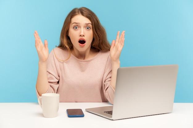Oh mijn god, wauw! jonge vrouw met geschokte uitdrukking camera kijken met open mond en het verhogen van de handen van verbazing, bezig met laptop vanuit kantoor aan huis. indoor studio-opname geïsoleerd, blauwe achtergrond