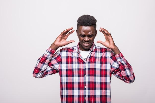 Oh nee. aantrekkelijke, ongelukkige afro-amerikaanse man met donkere ogen die een wit overhemd draagt en ontevreden kijkt en zijn handen op zijn hoofd heeft