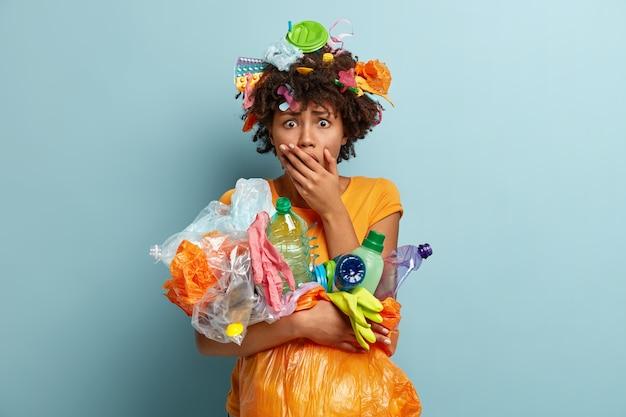 Oh nee, gebruik minder plastic. emotioneel verrast angstig vrouwtje bedekt mond, verzamelt plastic afval, staart met omg-uitdrukking, bezig met schoonmaken en recyclen, geïsoleerd tegen blauwe muur