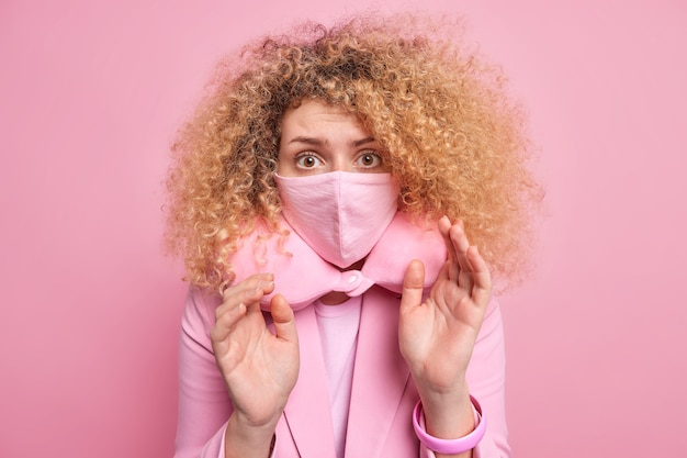 Oh nee houd social distancing. bange jonge vrouw met krullend haar die bang is voor iets houdt de handpalmen omhoog en draagt een beschermend masker om het nekkussen van het coronavirus te voorkomen voor comfortabele slaaphoudingen binnenshuis.