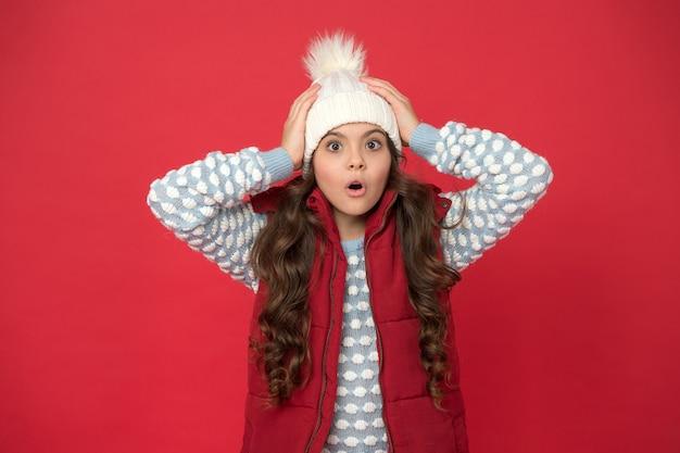Oh nee. verrast kind in gezellige gebreide outfit. wintermode voor kinderen. jeugd geluk. fijne wintervakantie en activiteit. weervoorspelling. warm deze winter. o mijn god.