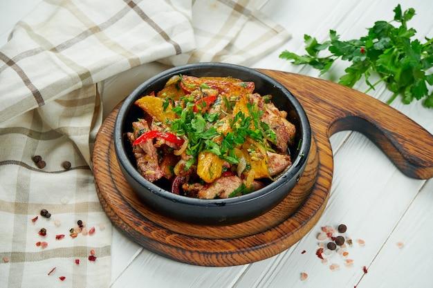 Ojahuri of gebakken vlees met aardappelen, uien en paprika in een zwarte pan.
