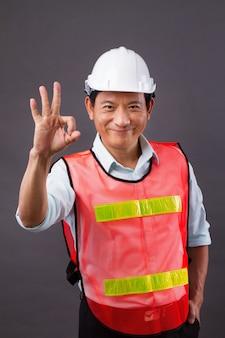 Ok handgebaar van zelfverzekerde, professionele aziatische mannelijke ingenieur, civiele bouw, bouwer, architect, arbeider
