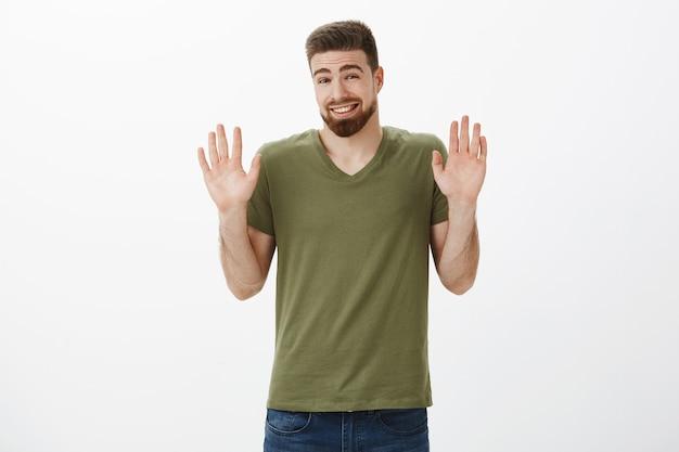 Oké, kalmeer, het spijt me. portret van knappe schattige jonge, bebaarde man die zich ongemakkelijk voelt en zich verontschuldigt voor weigering de handen op te steken in overgave met een dwaze glimlach die beschuldigingen doet en aanbod afwijst