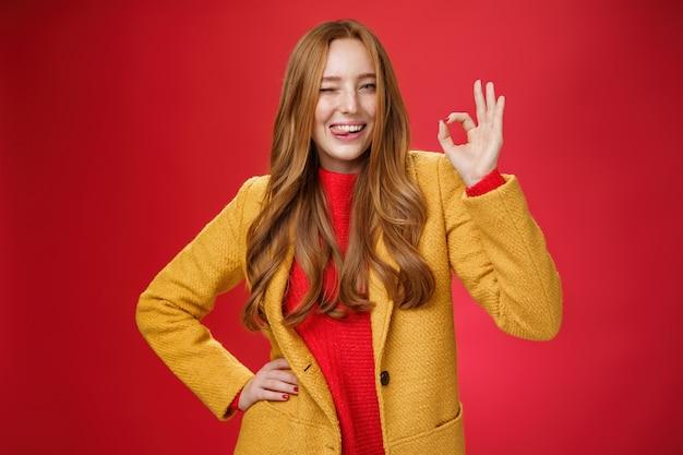 Oké snap het. portret van een zorgeloze, gelukkige en zelfverzekerde knappe charismatische gembervrouw met sproeten die knipogen en een tong tonen die vreugdevol een goed gebaar laat zien, die uitstekend werk over de rode muur leuk vindt.