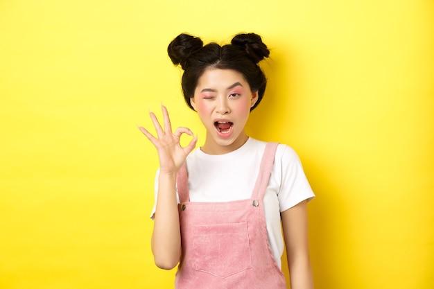 Oké. zelfverzekerd aziatisch vrouwelijk model met lichte make-up en zomerkleding, ok teken tonen, knipogen en ja zeggen, akkoord gaan en goedkeuren, geel.