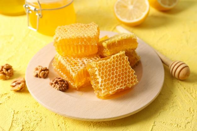 Okkernoot, honingraten, kruiken met honing, beer en citroen op gele achtergrond, close-up
