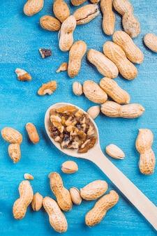 Okkernoot; pinda's en pistache op blauwe gestructureerde achtergrond