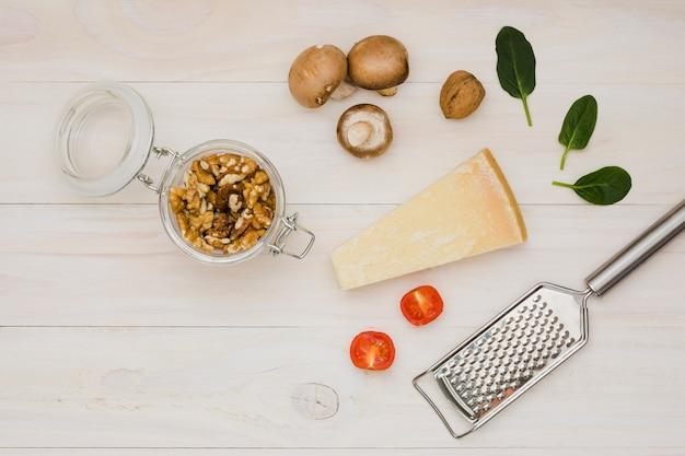 Okkernoot; tomaten; kaas; basilicum en champignons met metalen rasp op houten bureau