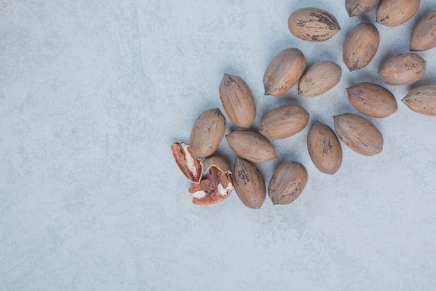 Okkernoten en okkernootpitten op marmeren achtergrond. hoge kwaliteit foto