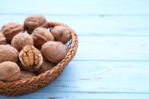 Okkernotenpitten in mand op blauwe houten achtergrond. walnoot gezond voedsel