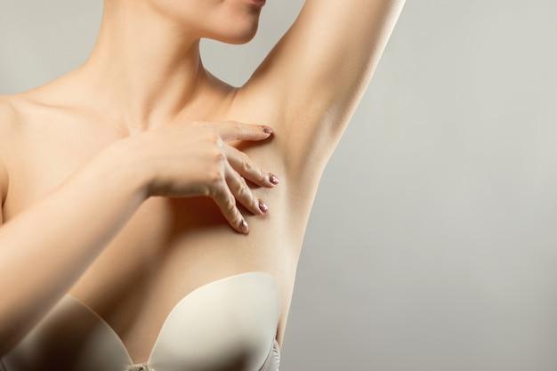 Oksel epileren, lacer ontharing. jonge vrouw houdt haar armen omhoog en toont schone oksels, depilati op een gladde, heldere huid. schoonheidsportret. huidverzorging.