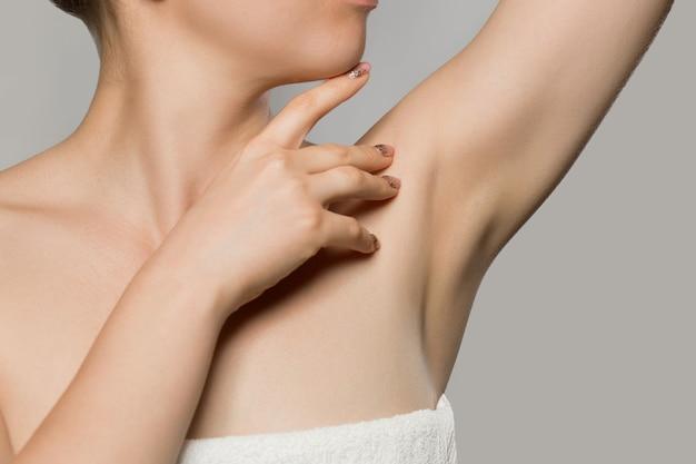 Oksel epileren, lacer ontharing. jonge vrouw houdt haar armen omhoog en toont schone oksels, ontharing gladde heldere huid. schoonheidsportret.