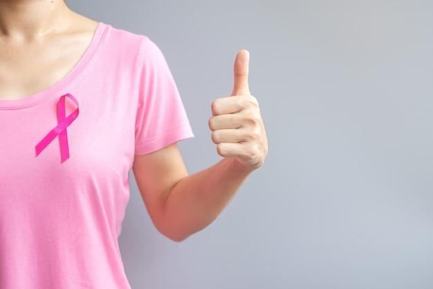 Oktober breast cancer awareness-maand, oudere vrouw in roze t-shirt met roze lint en duimteken voor het ondersteunen van mensen die leven en ziekte. internationaal vrouwen-, moeder- en wereldkankerdagconcept