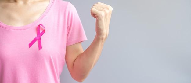 Oktober breast cancer awareness-maand, oudere vrouw in roze t-shirt met roze lint en vuistteken voor het ondersteunen van mensen die leven en ziekte. internationaal vrouwen-, moeder- en wereldkankerdagconcept