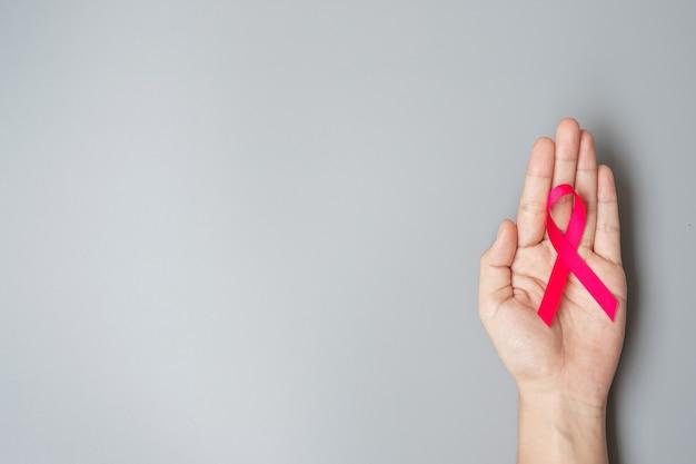 Oktober breast cancer awareness maand, volwassen vrouw hand met pink ribbon op grijze achtergrond voor het ondersteunen van mensen die leven en ziekte. internationaal vrouwen-, moeder- en wereldkankerdagconcept